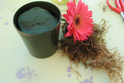 Supplies: CathysWraps flower pot and decorative sleeve, floral foam, a bit of moss and flowers.